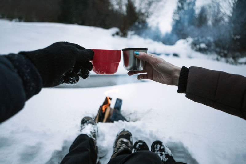 Low section of people toasting tea cups while sitting on snow covered field