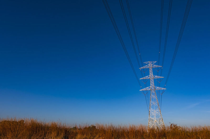 Electric pole and electric cable on the field in the countryside with blue sky.