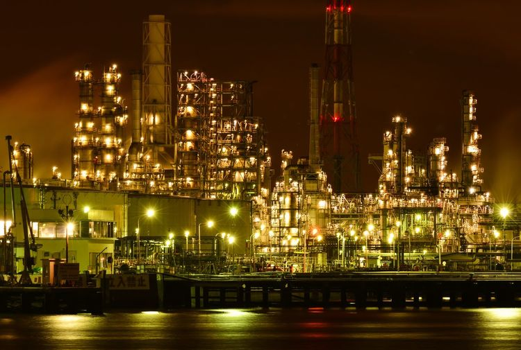 Illuminated industry by river against sky at night
