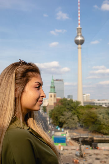 Smiling young woman looking away against berliner fernsehturm