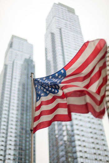 Low angle view of american flag against buildings