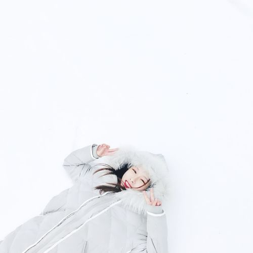 High angle portrait of woman gesturing peace sign while lying on snow