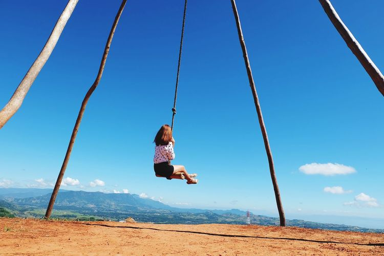 Rear View Of Girl On Swing Against Sky