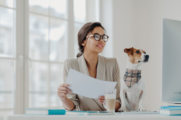 Smiling young woman with dog using computer on desk in office