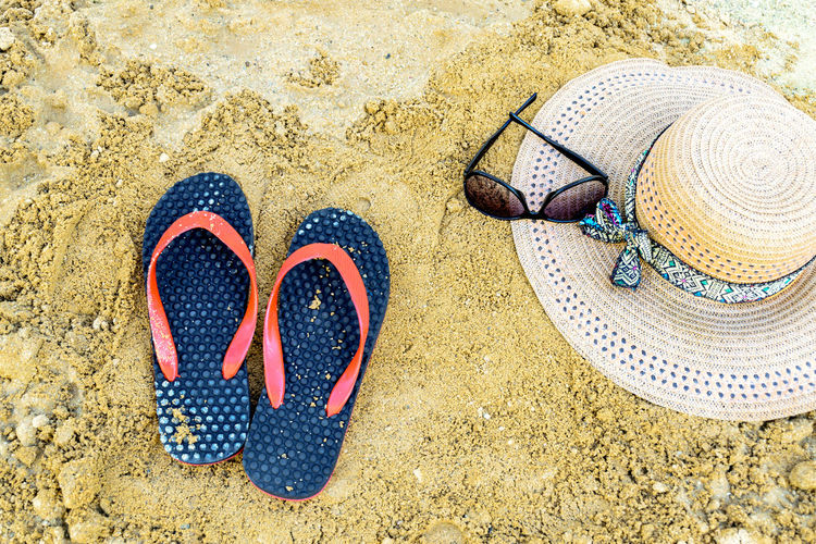 High angle view of flip-flops with sun hat and sunglasses on beach