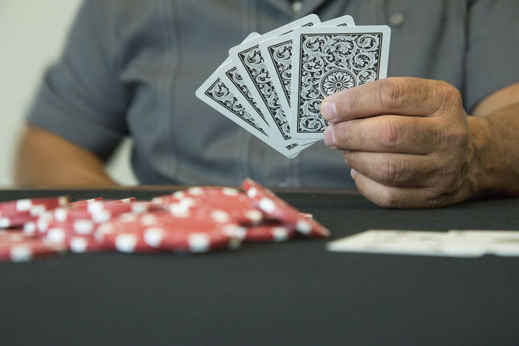 Midsection of man holding playing cards sitting at table