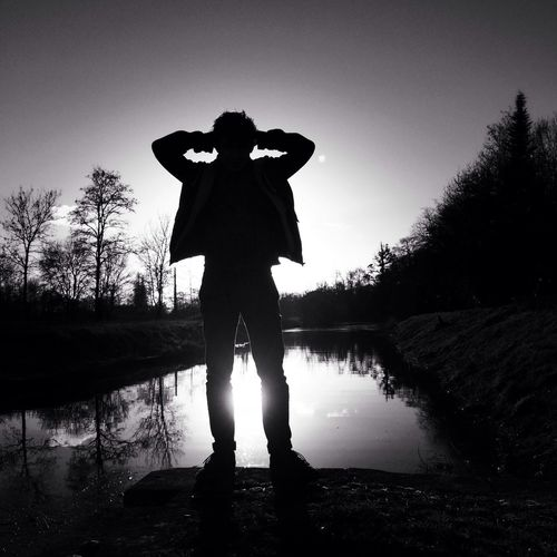 Silhouette of man standing at canal