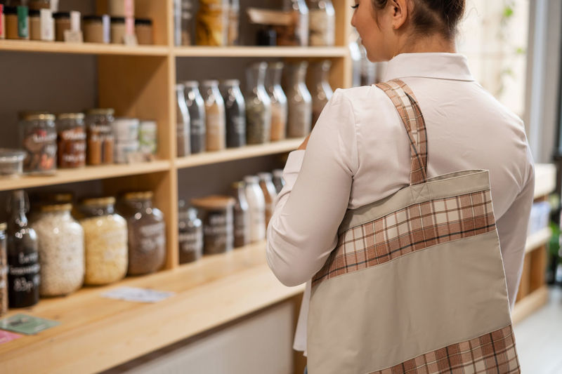 Rear view of woman standing at store