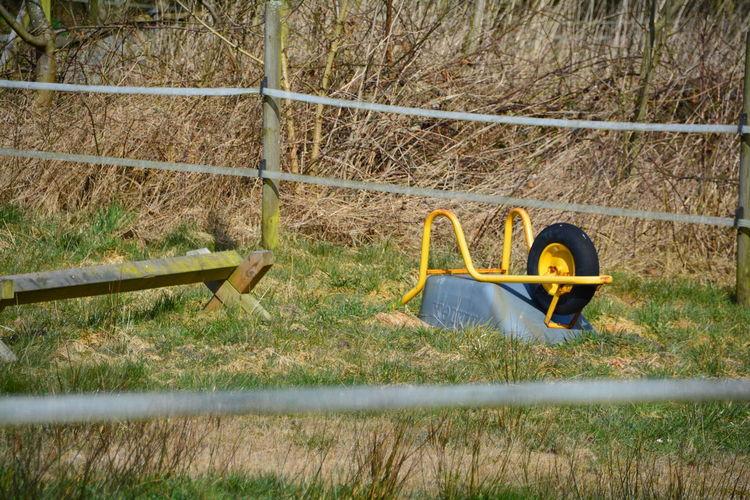 Upside down wheelbarrow on grassy field