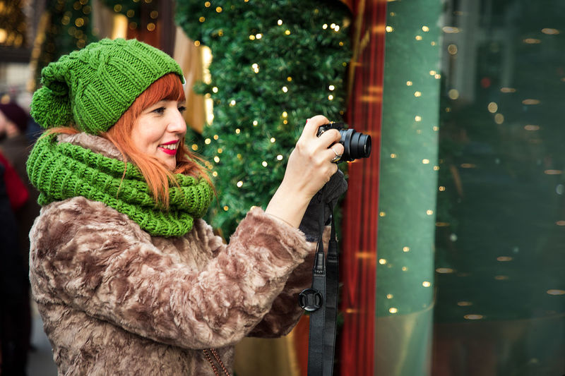 Women using camera taking pictures on a street with Christmas light decorations. Girl Enjoying Winter Holiday Season, Making picture Adult Camera Christmas Green Happy Hat Holiday London Taking Pictures Travel Winter Xmas Decorations Adults Only Beautiful Woman Day Evening Female Lifestyles One Person Outdoors Photographing Photography Smiling Street Warm Clothing