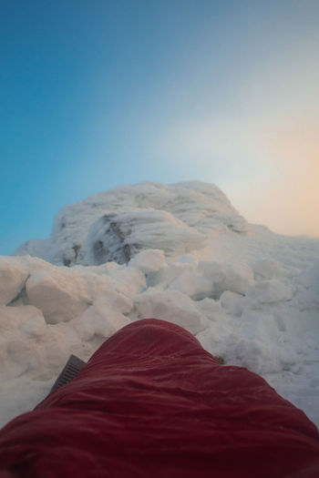 photo of a emergency snow bivouac on a winter alpine ridge Alpine Backpacking Camping Emergency Freezing Frozen Hiking Lifestyle Mountaineering Trekking Winter Active Adventure Arid Climate Beauty In Nature Bivouac Blue Clear Sky Climbing Cold Cold Temperature Copy Space Day Hobby Human Body Part Idyllic Low Section Mountain Mountain Peak Nature Non-urban Scene One Person Red Remote Scenics - Nature Shelter Sky Sleeping Bag Snow Snowcapped Mountain Snowshoeing Tent Trail Tranquil Scene Tranquility Winter