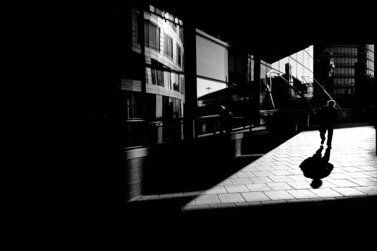 Silhouette person walking on street by building