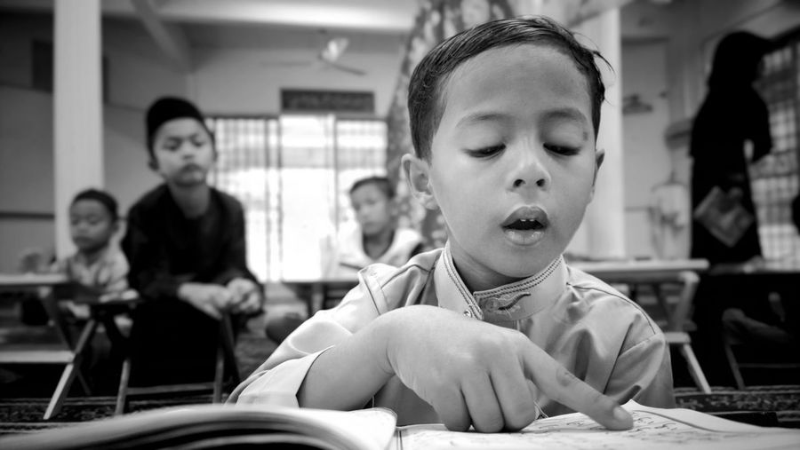 Boy Reading Book In Classroom