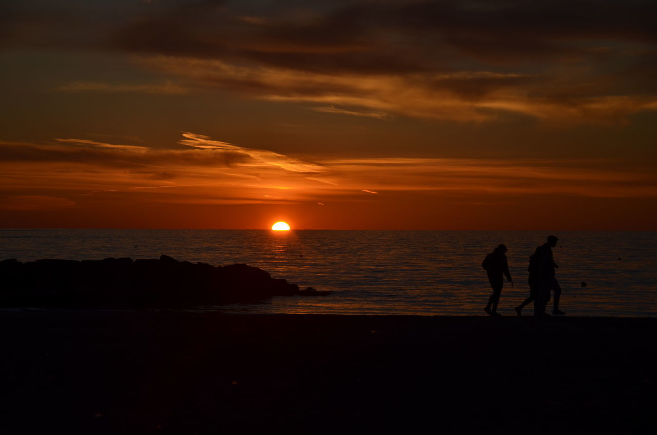 sunset, silhouette, sea, two people, beach, orange color, sky, scenics, togetherness, nature, beauty in nature, sun, real people, horizon over water, leisure activity, water, walking, tranquil scene, cloud - sky, tranquility, men, lifestyles, sand, outdoors, vacations, friendship, full length, people
