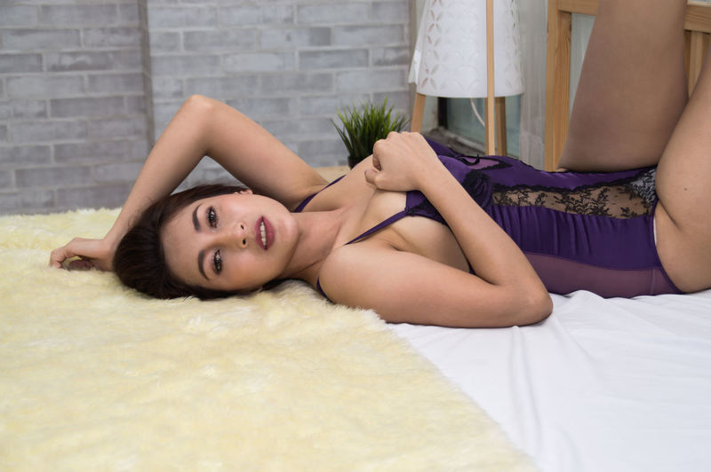 Seductive Woman Lying Down On Bed At Home