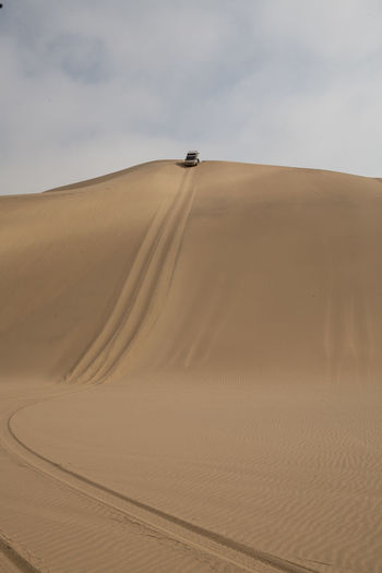 Distant View Of Off-Road Vehicle Moving Down Sand Dune Against Sky