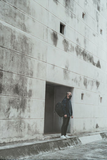 Full length of man standing against wall in city
