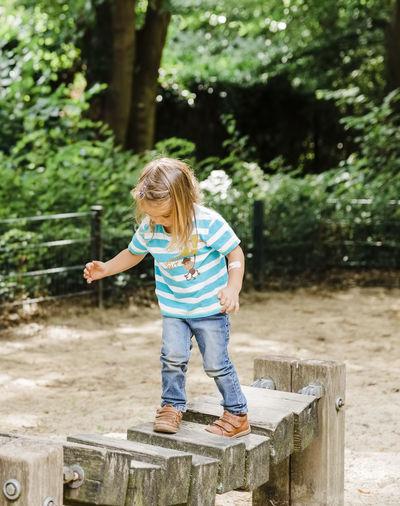 Girl walking on wood in park