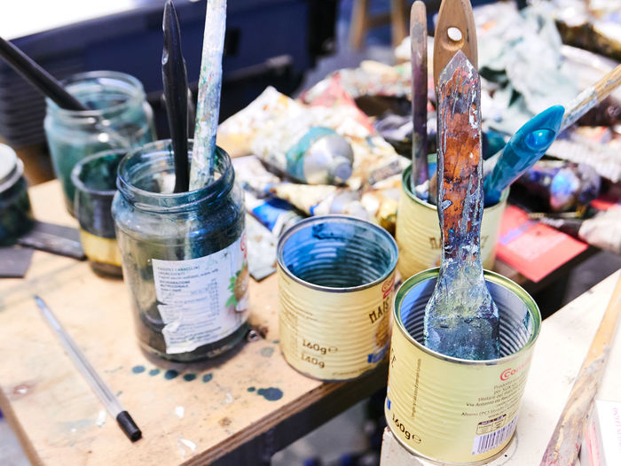 High angle view of paintbrushes in cans on table