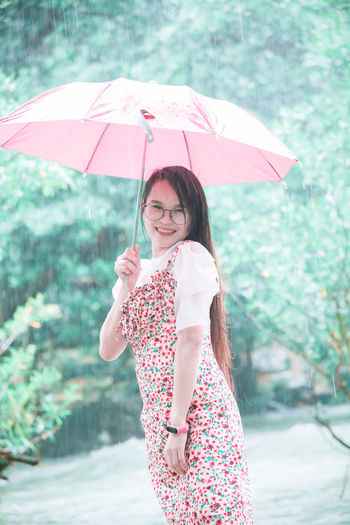 Portrait of young woman standing with umbrella during rainy season