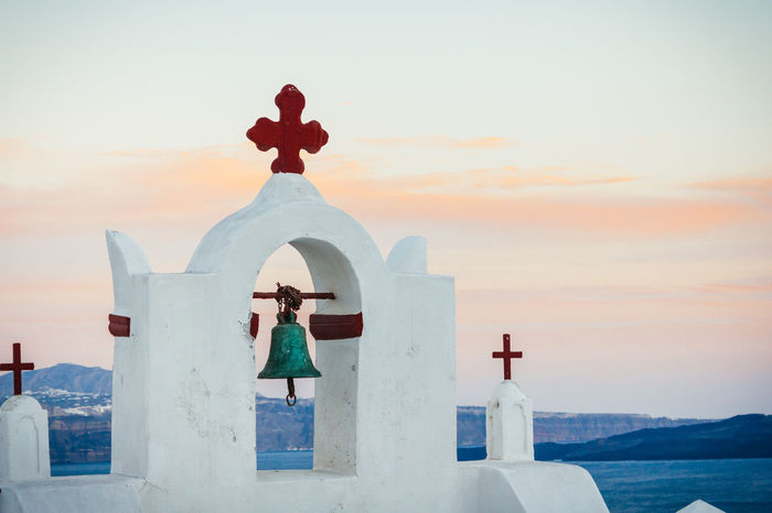 Aegean Sea Architecture Beauty In Nature Bell Church Cloud - Sky Cross Focus On Foreground Greek Islands Greek Symbols Nature Orange Color Outdoors Santorini Scenics Sea Sky Sunset Tradition Tranquil Scene Tranquility Travel Destinations