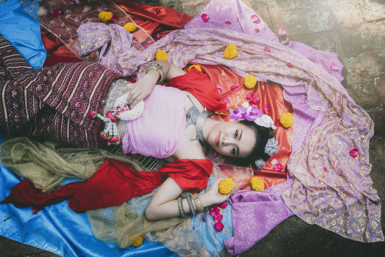 High angle view of woman in traditional clothing lying on footpath