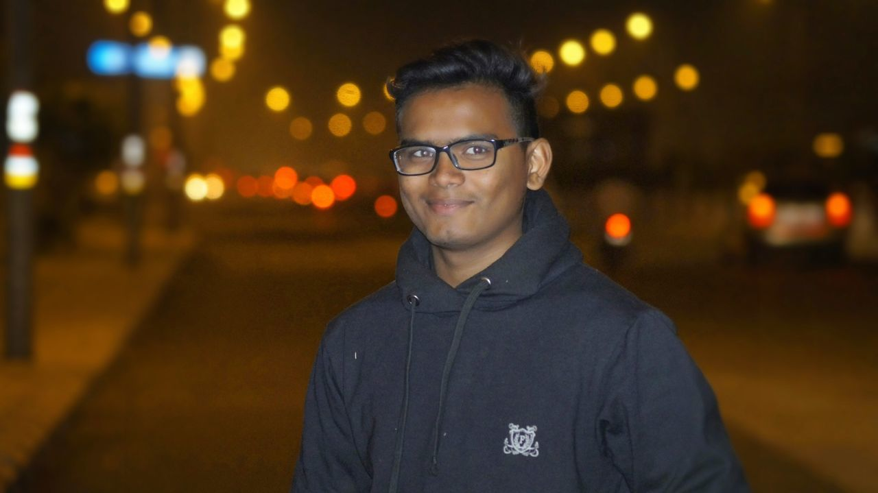 night, looking at camera, portrait, focus on foreground, illuminated, real people, one person, front view, young adult, lifestyles, young men, outdoors, eyeglasses, warm clothing, close-up, people