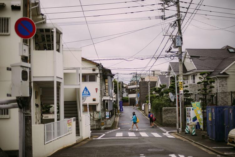Man walking on road amidst buildings in city