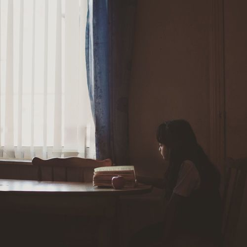 Girl reading book while sitting at home