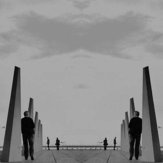 Mirror Image Of Man By Modern Sculpture Against Sky