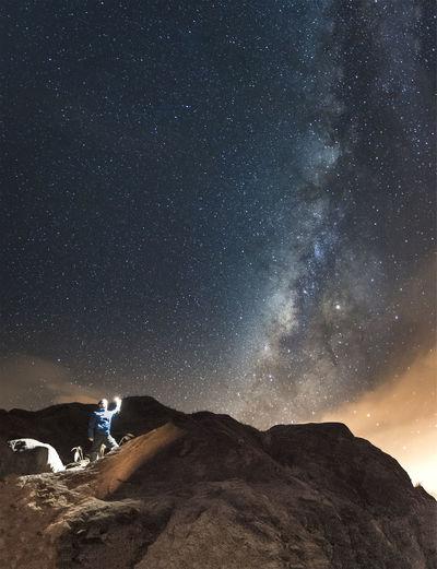 Man standing on rock against star field