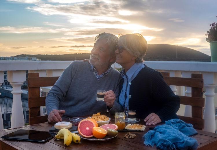 Senior couple enjoying food at sunset