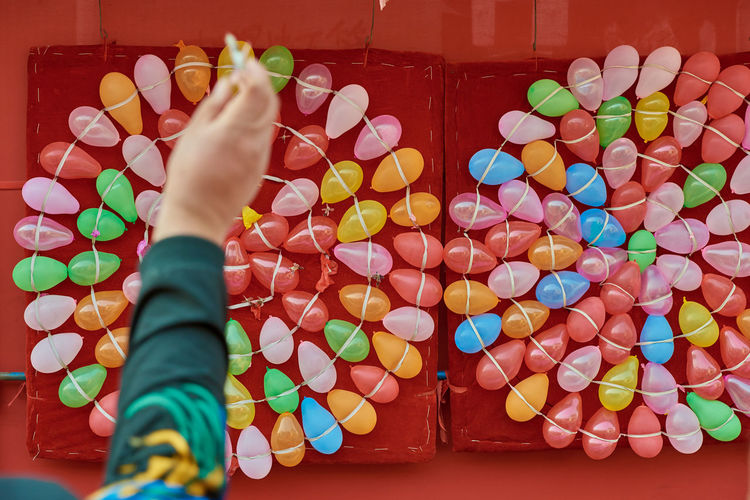 Cropped image of person throwing dart on colorful balloons