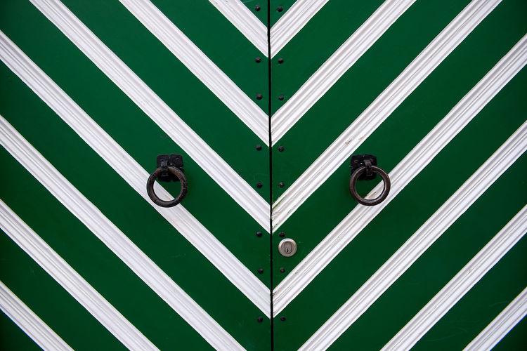 Ring knockers on green door
