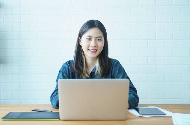 Portrait of a smiling young woman using laptop