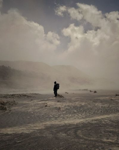 Man Standing On Landscape Against Cloudy Sky