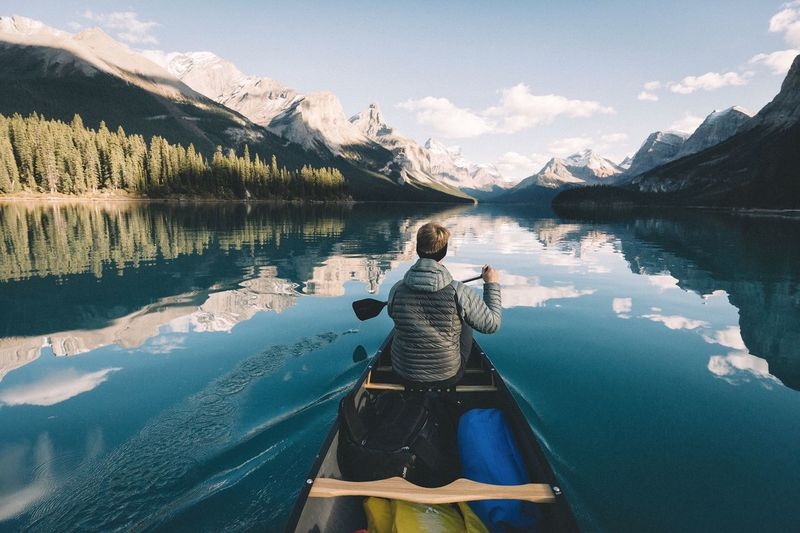 Rear View Of One Person Paddling On Maligne Lake