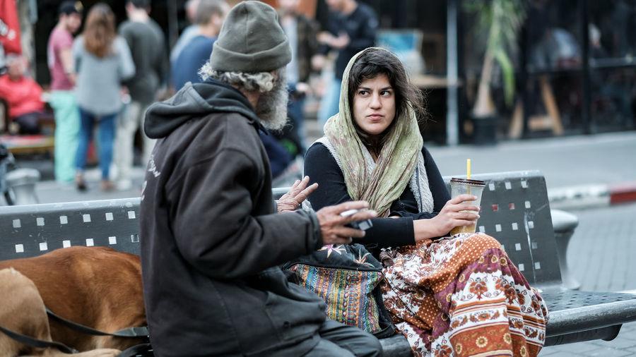 Friends sitting on street in city