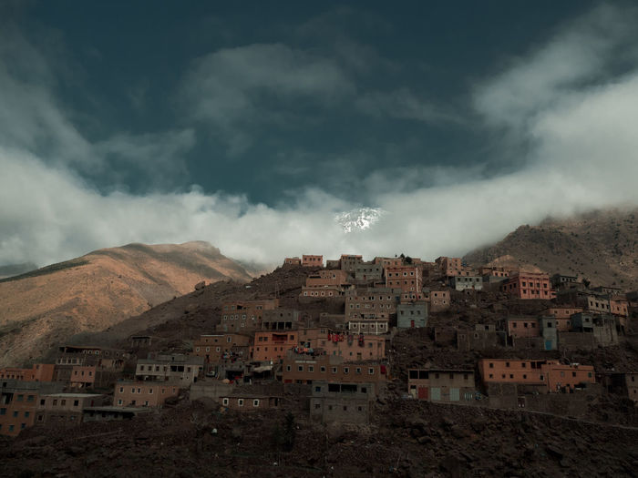 Peeking mountain peak behind the Berber village of Aroumd at the High Atlas mountains. EyeEmNewHere High Atlas Morocco Morocco Africa Berber  Berbervillage Building Cloud - Sky High Atlas Mountains Land Landscape Mountain Nature No People Outdoors Scenics - Nature Sky Town Village The Great Outdoors - 2018 EyeEm Awards The Traveler - 2018 EyeEm Awards The Architect - 2018 EyeEm Awards