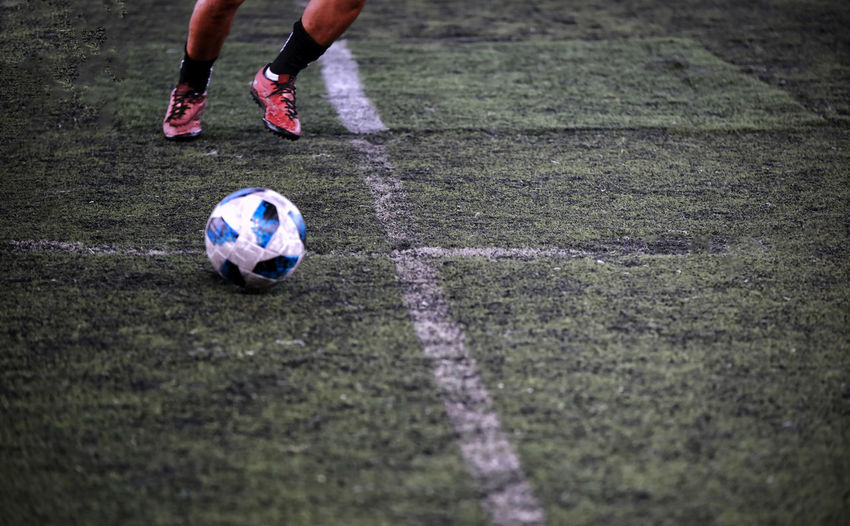 Low section of man playing with soccer ball on field
