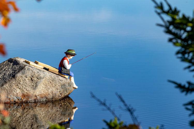 Man working on rock against blue sky