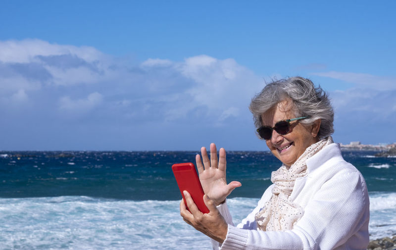 Smiling senior woman talking on video call at beach against sky