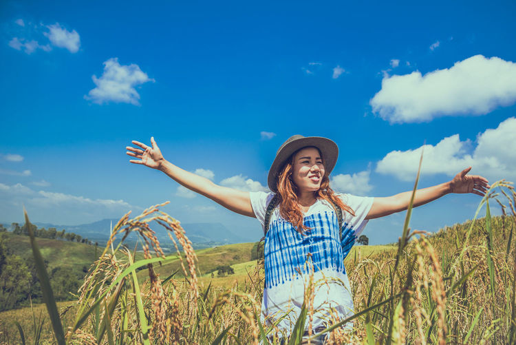 Smiling woman wearing hat standing on field against sky