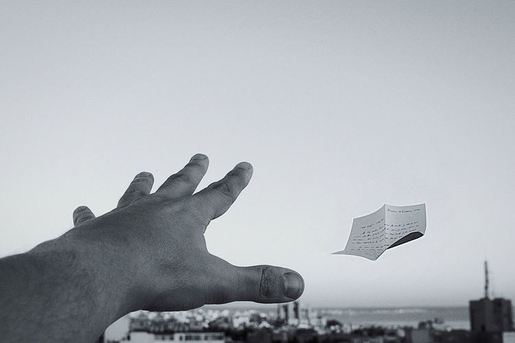 Cropped hand of person attempting to catch paper against sky