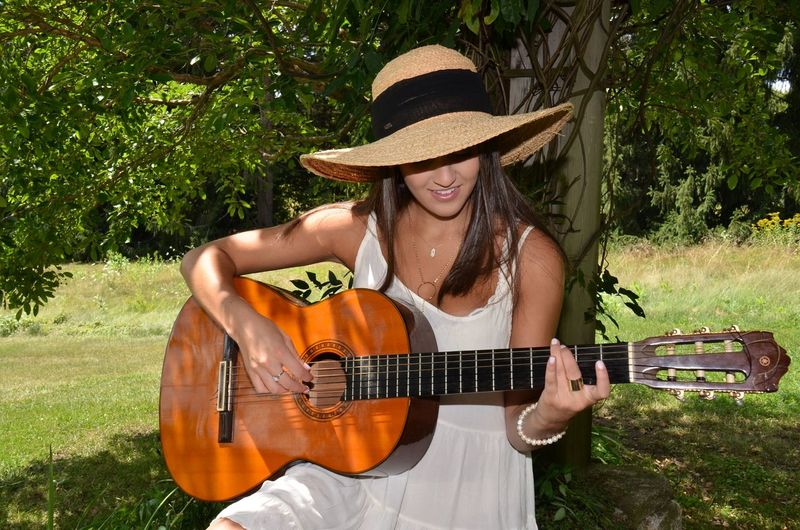 Beautiful woman playing guitar on field