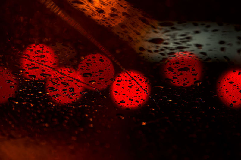 Night lights of urban traffic seen through the windshield in rainy weather. Abstract background of urban city in night with light bokeh . Concept of night city life and cars Bright Cars City Dark Drops Night Lights Raindrops Road Traffic Weather Bokeh Brake Lights darkness and light Ilumination Night Rainy Red Road Sign Stop Stop Light Stop Sign Traffic Lights Urban Window Windshield