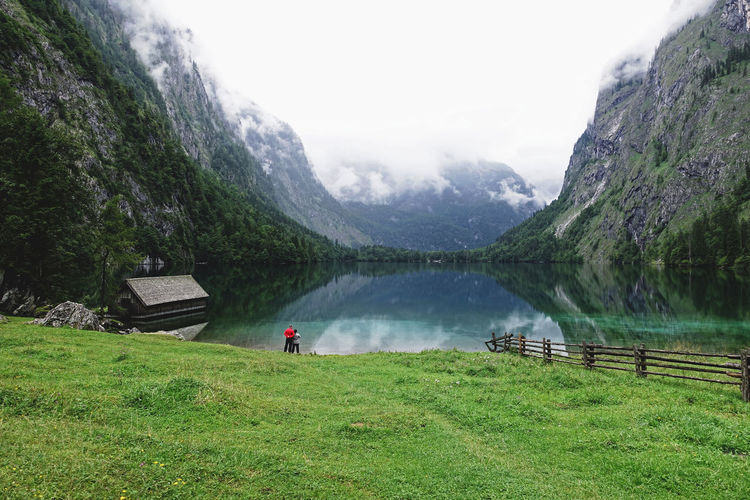 Lake Water Mountain Mountain Range Grass Beauty In Nature Scenics - Nature Nature Non-urban Scene Outdoors Lifestyles Green Color Sky Land Tranquil Scene Plant House Couple Togetherness Happiness Relaxing Enjoying Life Landscape Reflection Life Moments Of Happiness It's About The Journey