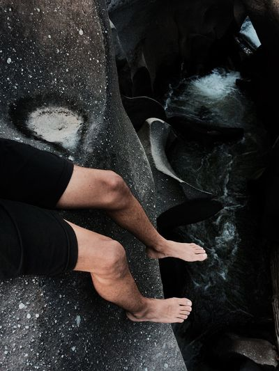 Low section of man sitting on black rock formation by sea