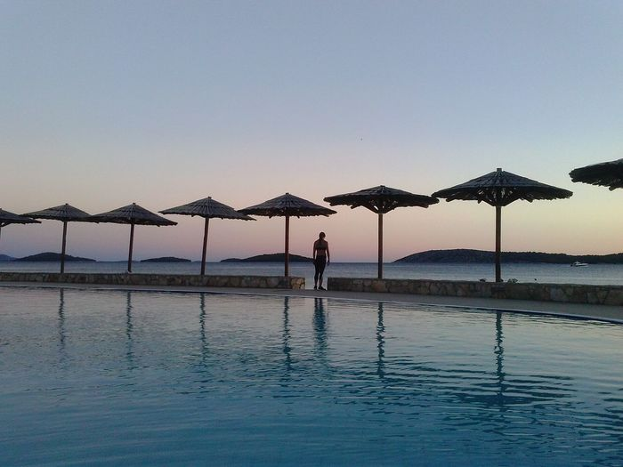 Rear view of woman standing in between infinity pool and sea at sunset