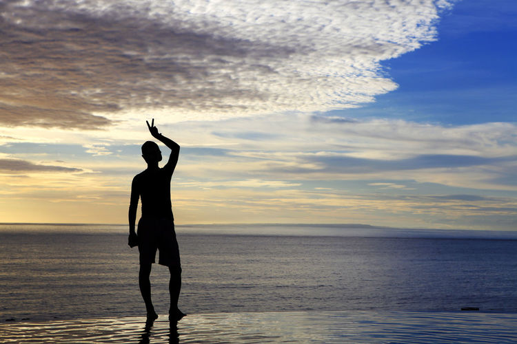 Silhouette man gesturing while standing by infinity pool at sea against sky during sunset